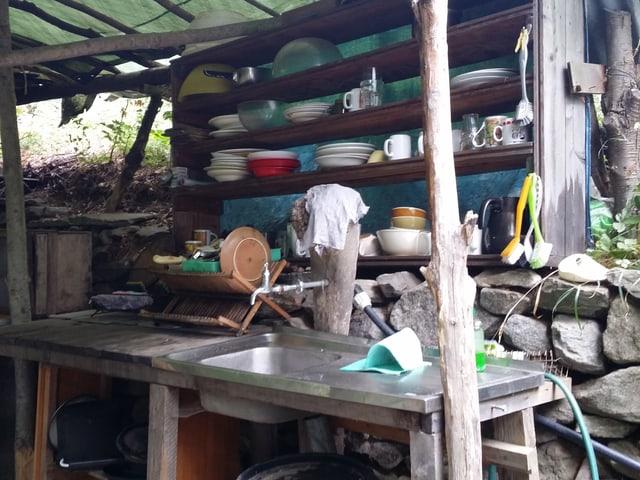 Ein einfacher Verschlag mit einem Becken und Tellern, die auf selbstgezimmerten Holztablaren stehen.