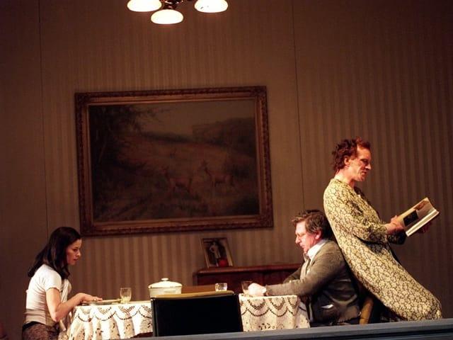 Auf der Bühne: Zwei Personen, Frau und Mann, sitzen sich an einem grösseren Tisch gegenüber. Ein weiterer Mann lehnt sich mit seinem Rücken an der Stuhllehne des sitzenden Mannes an und liest in einem Magazin.