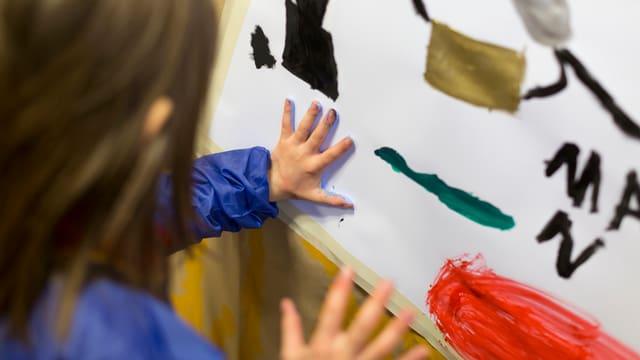 Ein Mädchen malt auf ein Papier