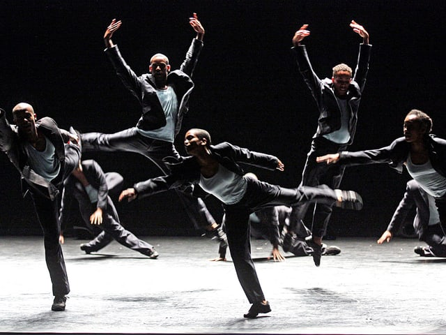 Männer springen in grauen Anzügen über die Bühne – in einer Mischung aus klassischem Ballett und zeitgenössischem Tanz.