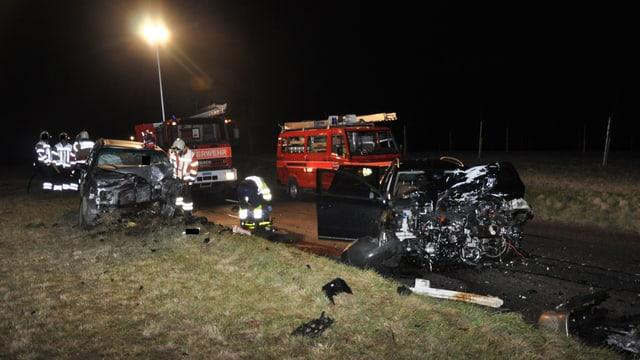 Zwei total zerstörte Fahrzeug, dahinter Einsatzfahrzeuge der Feuerwehr.