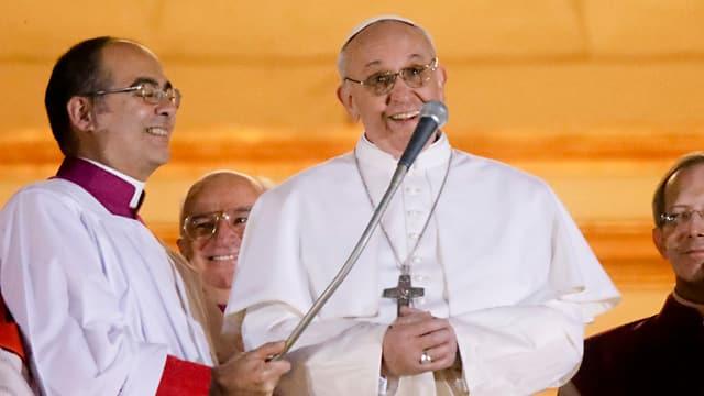 Der neue Papst Franziskus mit weissen Gewand hinter einem Mikrofon.
