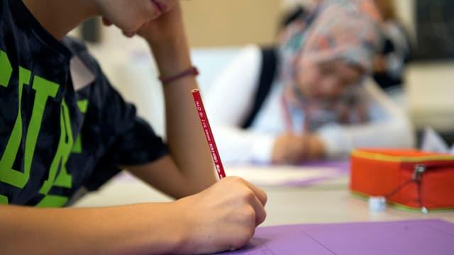 Ein Schüler schreibt auf ein Blatt.