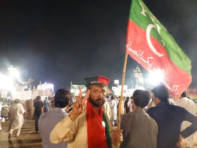 Ein Mann mit einer Fahne formt ein Victory-Zeichen mit Zeige- und Mittelfinger.
