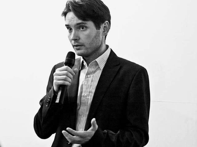 Ein Mann in einem schwarzen Anzug mit einem MIkrofon in der Hand.