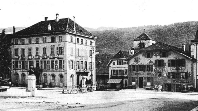 Ein grosses Haus, davor der Dorfplatz mit Brunnen, daneben ein Bauernhaus.