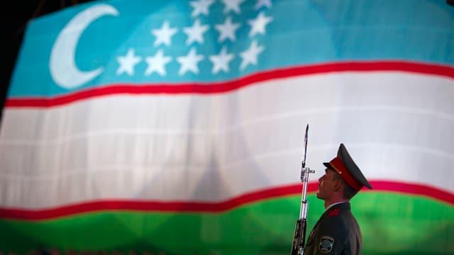 Ein Soldat mit Gewehr vor einer usbekischen Flagge.