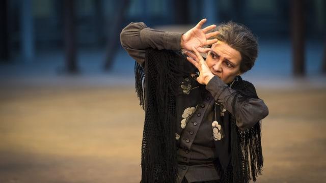 Eine Darstellerin hält abwehrend die Hände vors Gesicht.