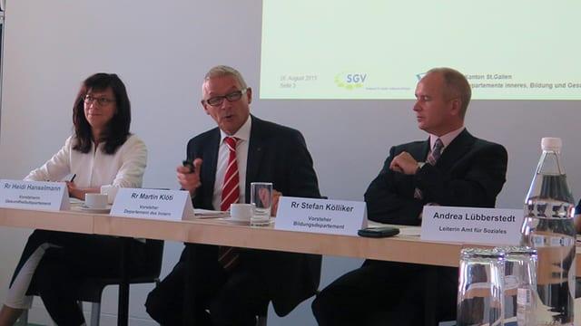 Drei Regierungsräte sitzen an einem Tisch, im Hintergrund eine Powerpoint Präsentation.