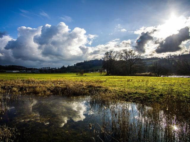 Die Bise sorgte für einen lebhaften Wechsel aus Sonne und Wolken. Dazu sieht man das Spiegelbild in einem kleinen See.