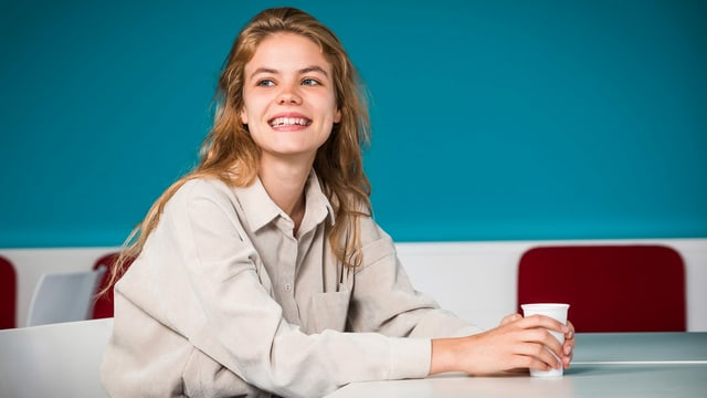 Eine junge Frau sitzt lachend an einem Tisch.