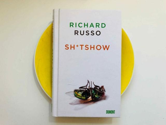Der Roman «Sh*tshow» von Richard Russo liegt auf einem gelben Teller