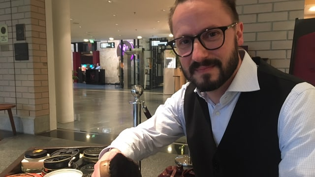 Schuhputzer Claudio Bühlmann hat eine Bürste in der Hand.