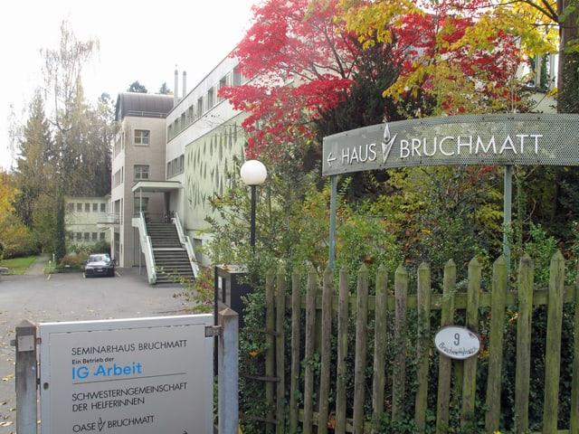 Eingang zu einem Haus mit einem grossen Garten, davor ein Schild. Darauf steht «Haus Bruchmatt».