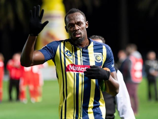 Usain Bolt winkt in die Kamera.