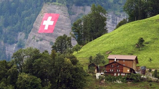 Eine Schweizer Fahne ist an eine Felswand gehängt. Davor zu sehen sind hellgrüne Bergwiesen und dunkelgrüne Bäume. Dazu ein Weiler mit zwei Holzhäusern.