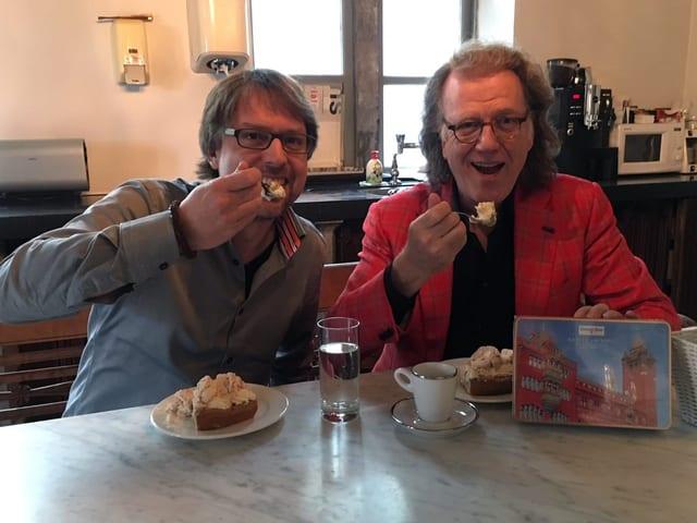 Zwei Männer sitzen an einem langen Esstisch und geniessen eine Nachspeise.