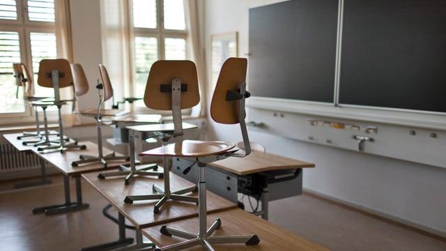 Klassenzimmer mit Stühlen auf den Tischen und einer Wandtafel im Hintergrund.