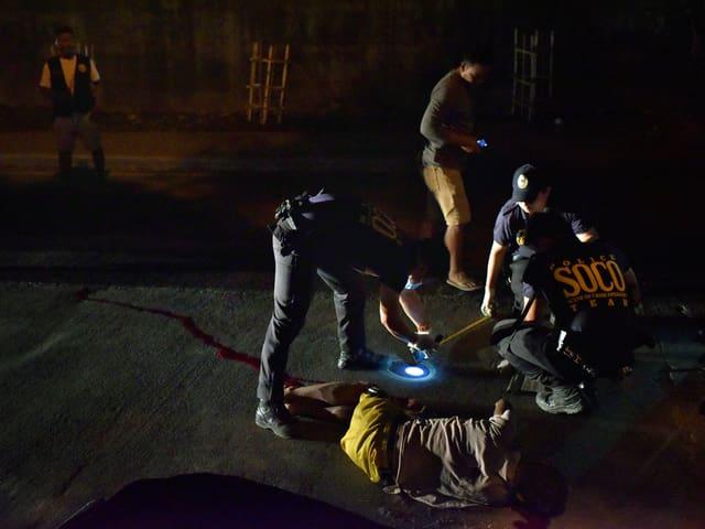 Zwei Polizisten beugen sich im Dunkeln über einen erschossenen mutmasslichen Drogendelinquenten.