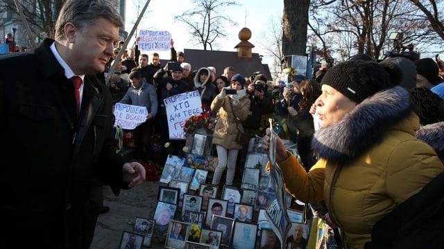 Präsident Poroschenko spricht an der Gedenkfeier mit einer protestierenden Frau