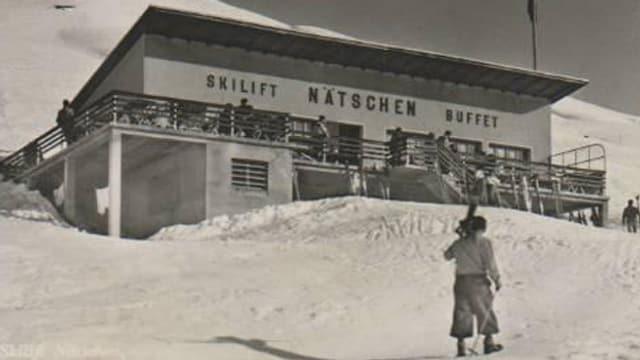 Man mit Skiern vor einem alten Bergrestaurant.