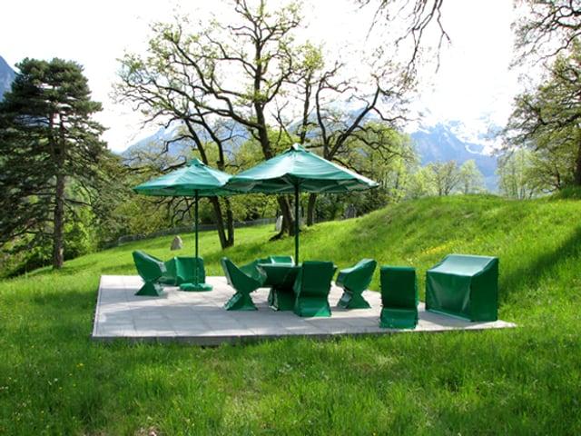 Die Installation «Eden» (2008) von Joëlle Flumet: zwei Sonnenschirme und Stühle mit grüner Schutzfolie abgedeckt