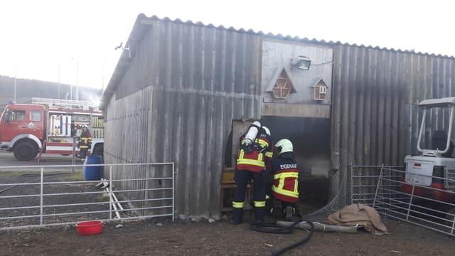 Stall mit Wellblech, davor zwei Feuerwehrmänner.