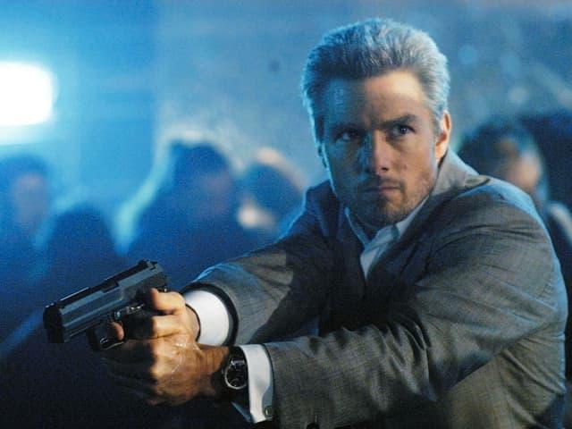 Der Auftragskiller Vincent hält eine Pistole in der Hand.