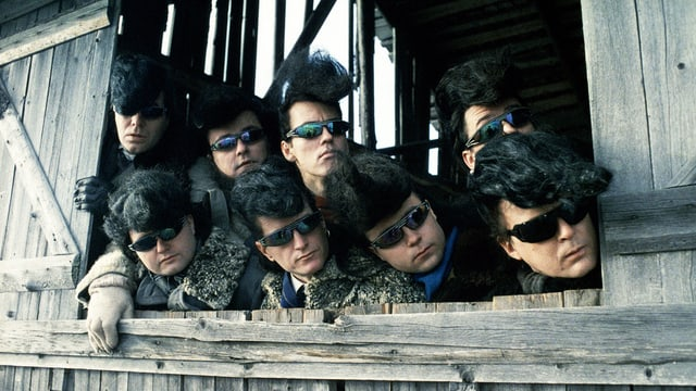 Männer mit Sonnenbrille und Elivsfrisuren schauen aus einem Stall.