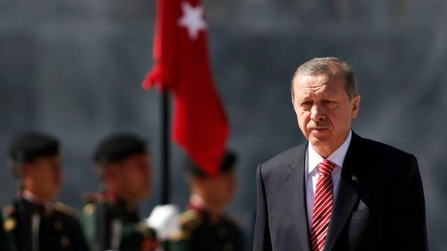 Der türkische Präsident Recep Tayyip Erdogan im Porträt vor der türkischen Flagge im Hintergrund.