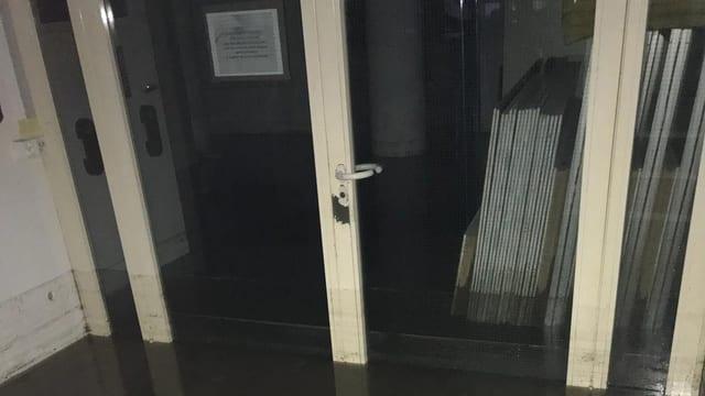 Überflutetes Gebäude: Türe, am Boden ein Streifen Wasser