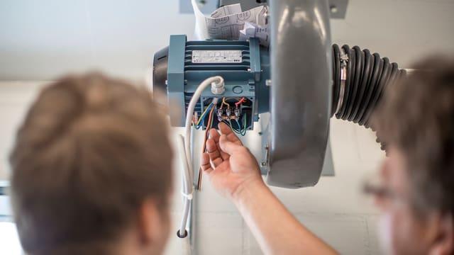 Zwei Handwerker arbeiten innen an einer Art Stromkasten.