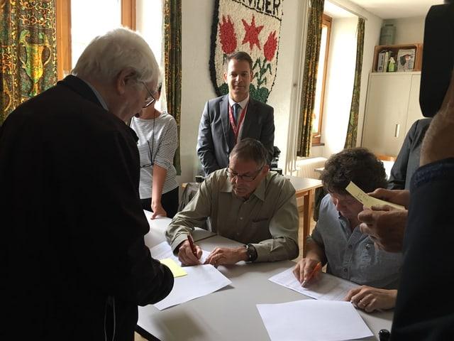 Abstimmungslokal mit Menschen am Tisch.