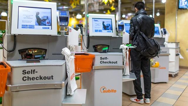 Ein Kunde scannt selbstständig seine Einkäufe ein.