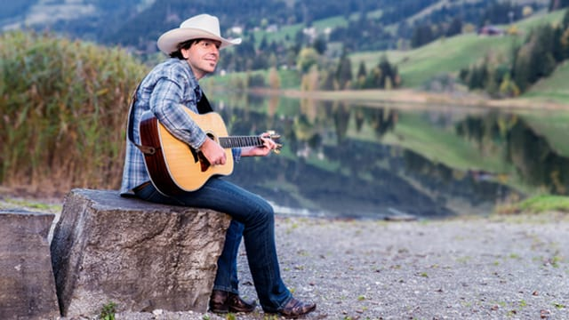 Udo Brügger mit Cowboyhut und Gitarre, sitzt auf einem Stein vor einem See.