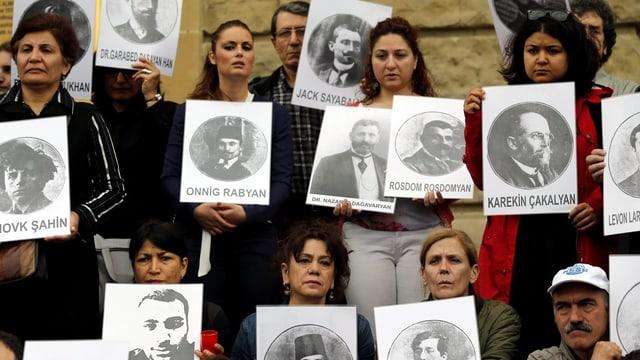 Menschen halten Porträtbilder von ermordeten Armeniern in den Händen.
