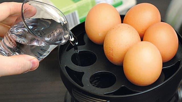 Eine Frau füllt Wasser in einen Eierkocher.