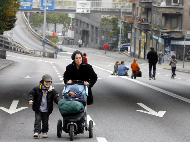 Frau mit Kinderwagen auf Autofreier Strasse, andere Menschen sitzen mitten auf der Strasse