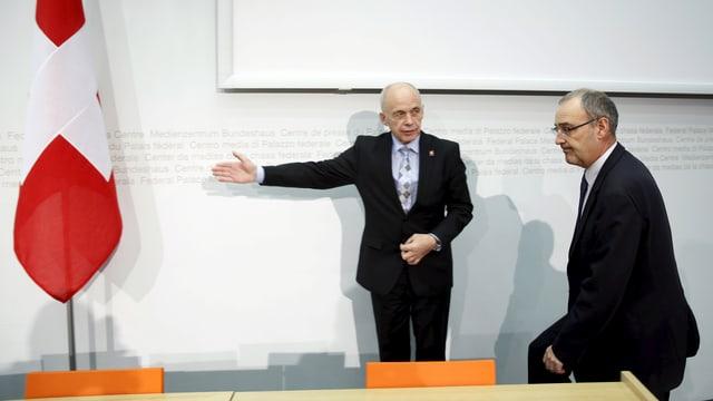 Ueli Maurer und Guy Parmelin vor einer Medienkonferenz, im Hintergrund eine Schweizer Fahne.