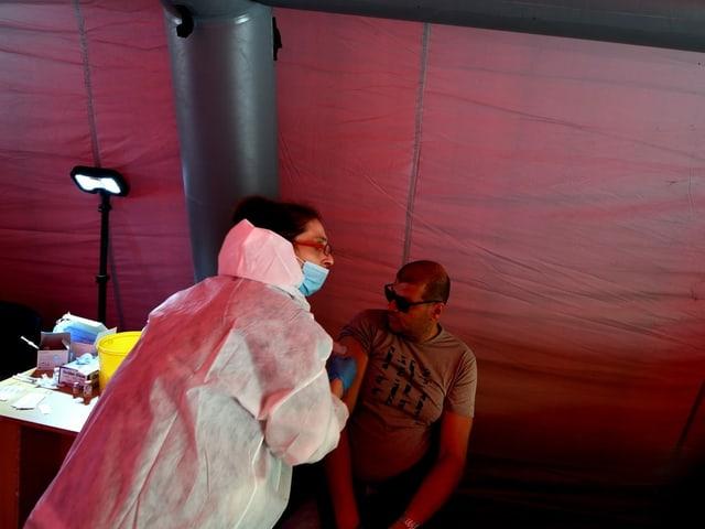 Eine medizinische Fachfrau spritzt einen Impfstoff in die Schulter eines Mannes.