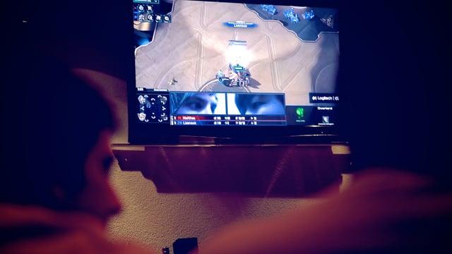 Zwei Köpfe vor einem TV-Bildschirm mit Starcraft.