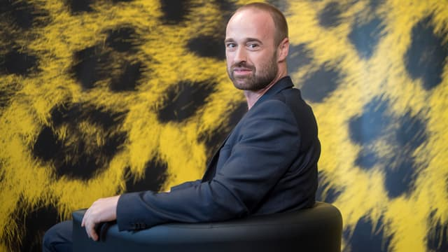 Das Bild zeigt Regisseur Dominik Locher vor einer gelb-schwarzen Wand.