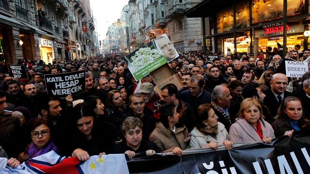 Personen mit Plakaten vor einem Banner auf der Strasse stehend.