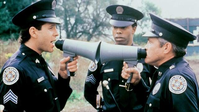 Filmszene Zwei Polizisten sprechen aus nächster Distanz durch zwei Megaphone miteinander