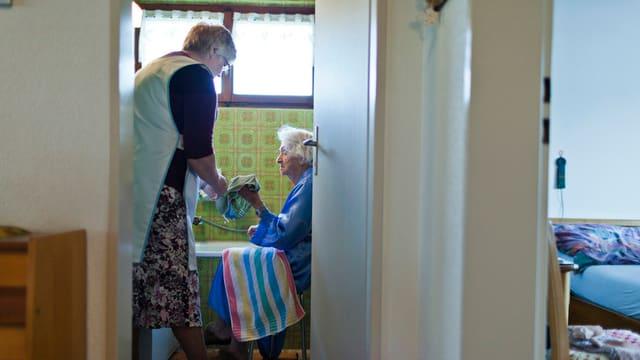 Eine ältere Pflegefachfrau kümmert sich um eine alte Frau im Bad.