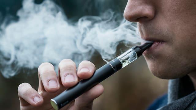 Mann, der an einer E-Zigarette zieht.