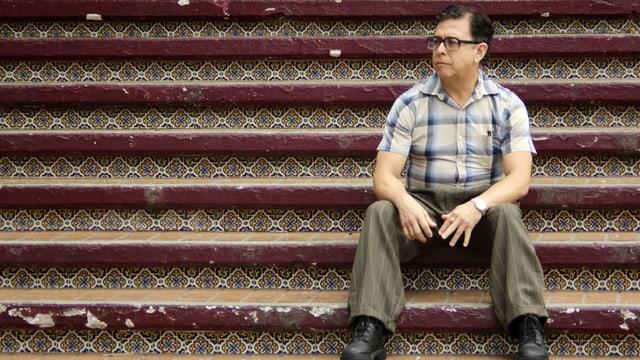 Ein älterer Mann mit dunklen Haaren, schwarzer Brille und kariertem Hemd sitzt auf einer Treppe.