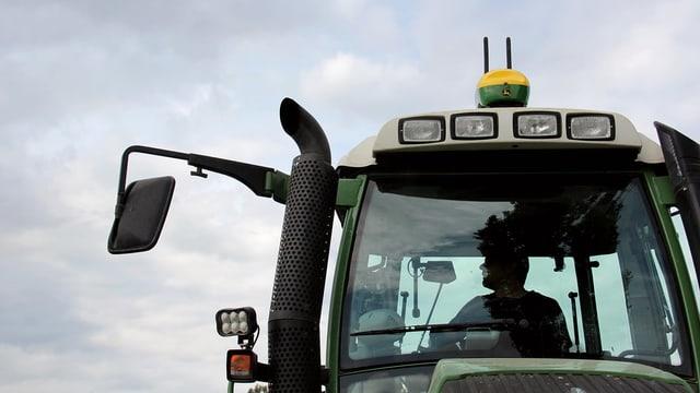 Ein Traktor, auf dem Dach ist eine grün-gelbe GPS-Box mit zwei Antennen montiert.