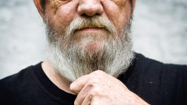 Ein Bild von einem älteren Herrn, der seinen Bart in der Hand hält.