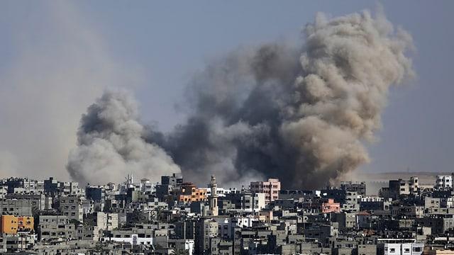 Rauchwolken am Horizont über dem Gazastreifen. Dicht besiedeltes Gebiet im Vorderdrund.